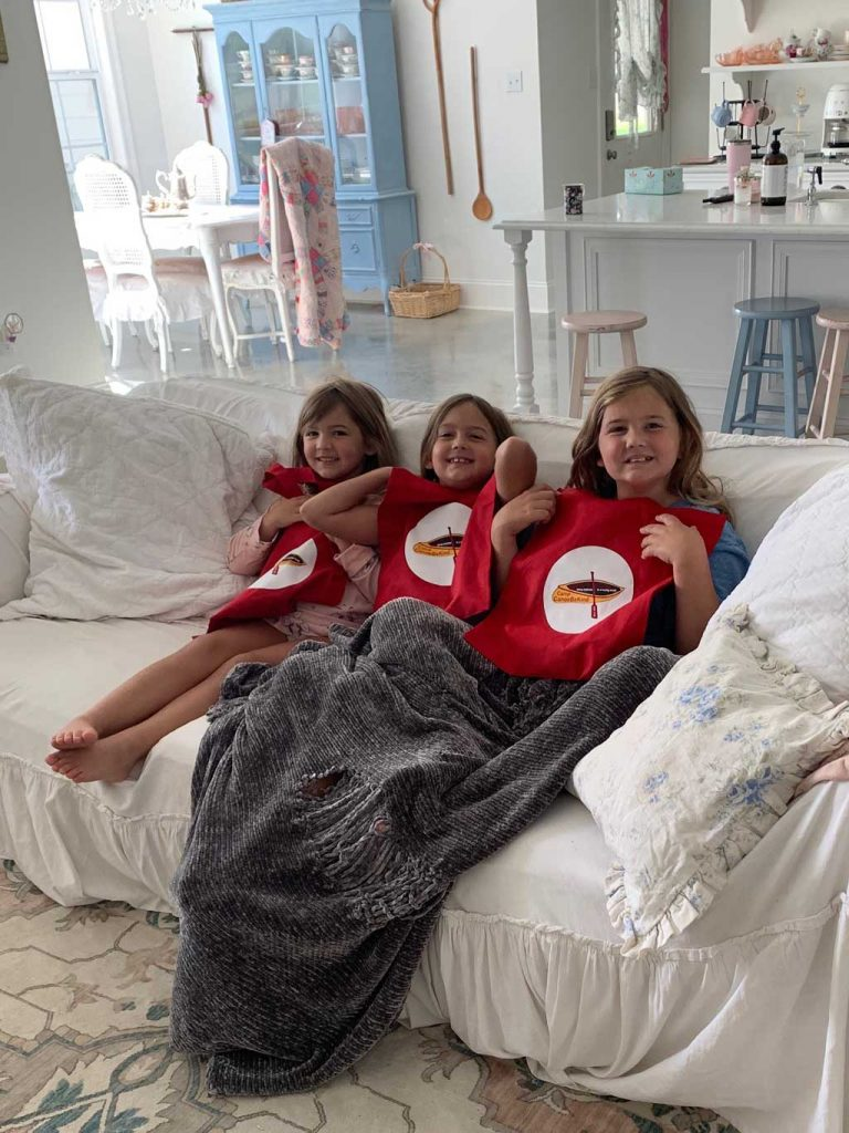 Three sisters show off their Camp Canoe-Be-Kind red bags of courage.