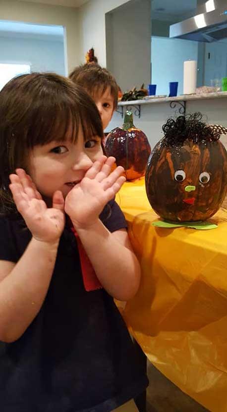 LANDers After School Children Pose with Pumpkin Art