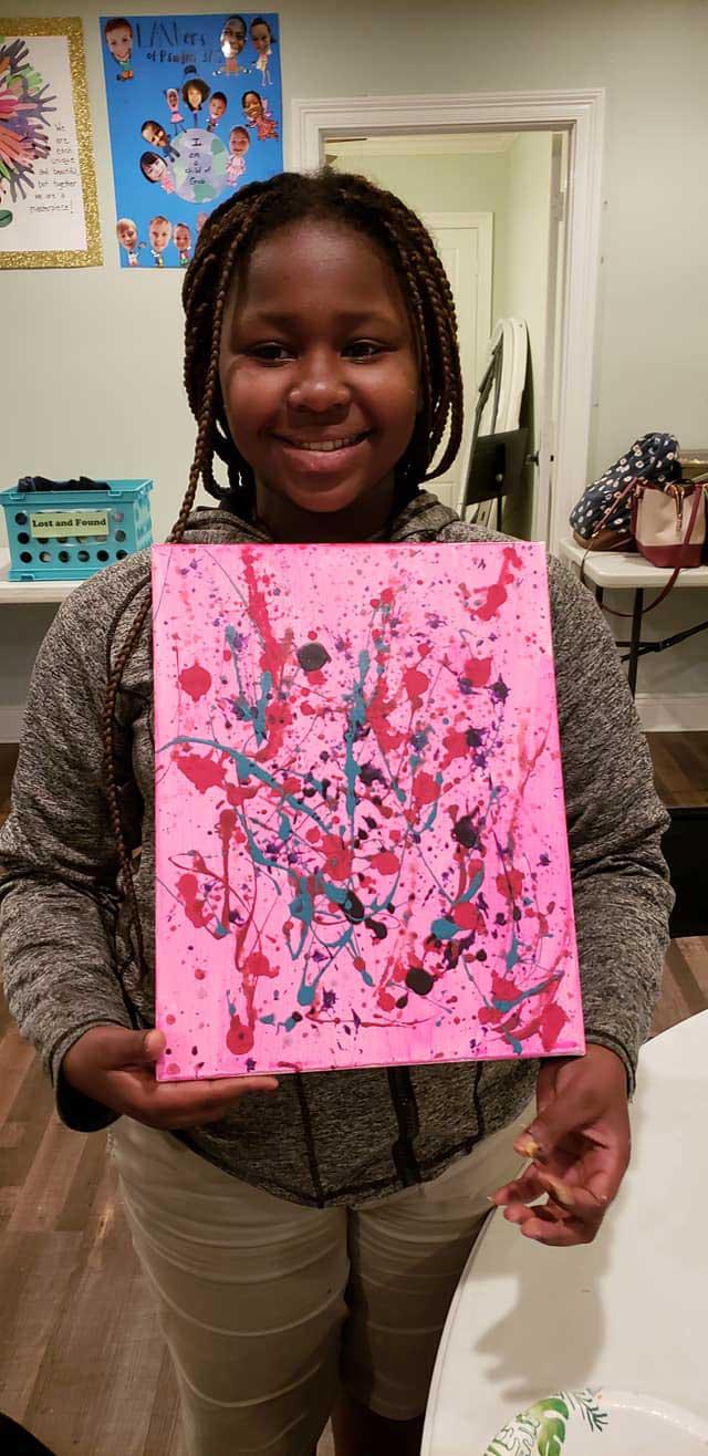 Girl with Artwork in the LANDers After-School Program