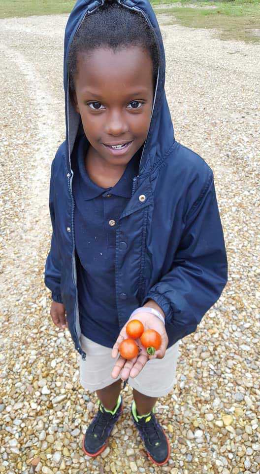 LANDers After School Child Poses with Tomatoes