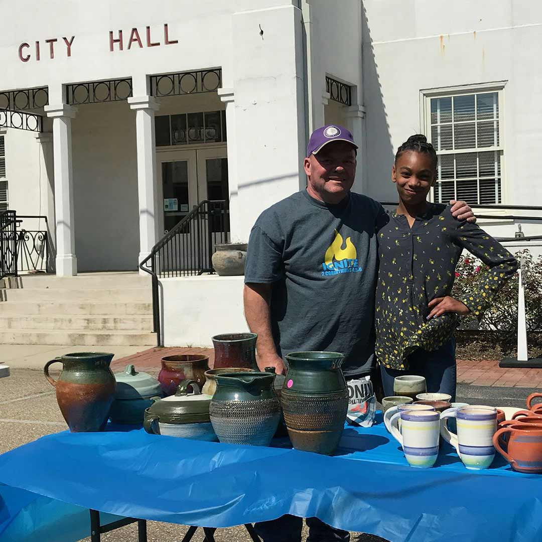 Pottery Teacher and a Young Artists' Academy Student Stand in front of City Hall
