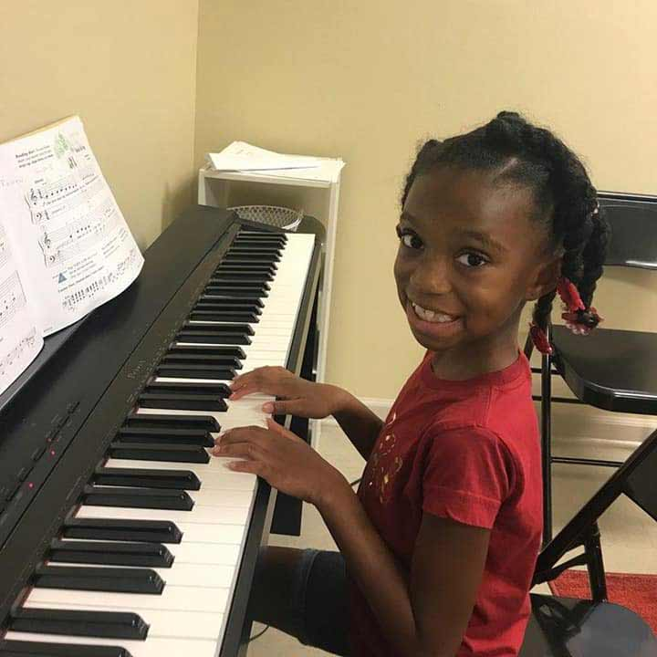 A young girl plays the piano at the YAA Arts Classes in Denham Springs